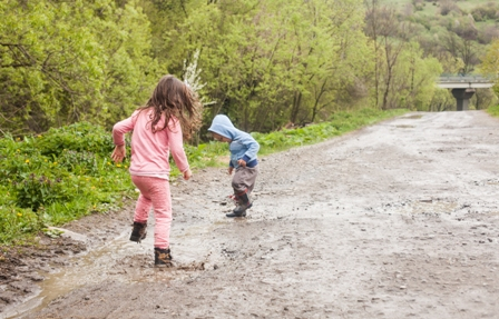 kids playing in mud puddle