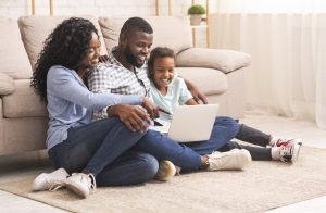 Black family of three using laptop together at home