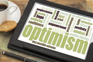 optimism word cloud on a digital tablet with a cup of coffee.