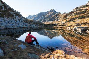 Male hiker takes a rest sitting next a mountain lake.
