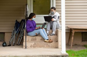 Two friends study together at home as part of their school's remote learning group. <br />