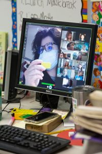 A computer screen shows a second-grade teacher leading a lesson for her remote learning students.